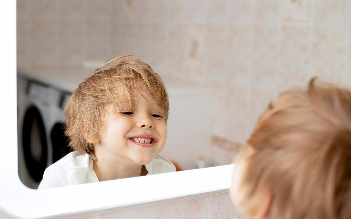 Young boy smiling at himself in the mirror to see the symmetry in his face.
