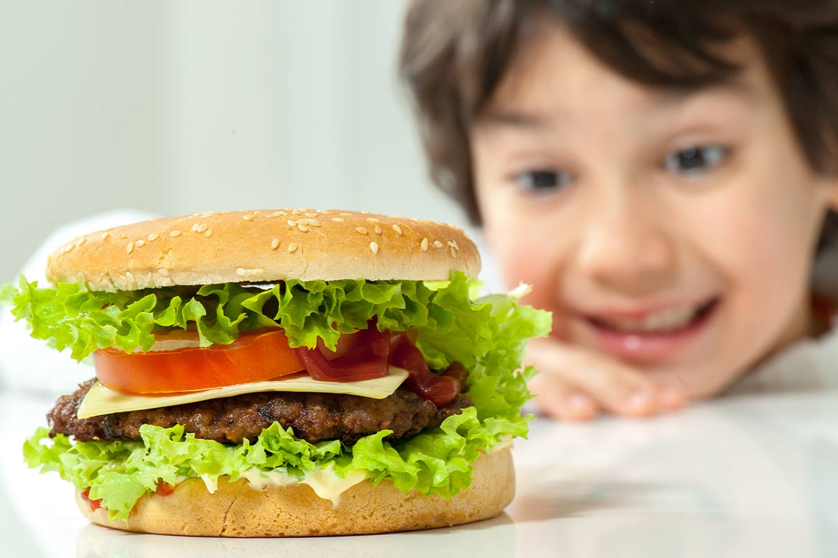 A burger is on the table in the foreground, behind it a young boy is smiling and looking at the burger.