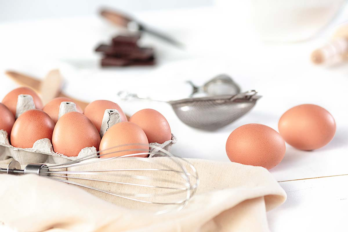 Lots of eggs and a whisk to use to make a burger cake.