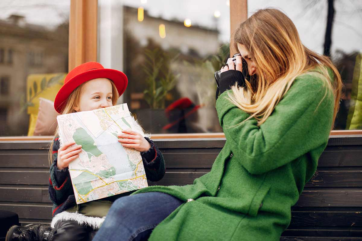 Mum sat on a bench taking a photo of her daughter who is holding a map.