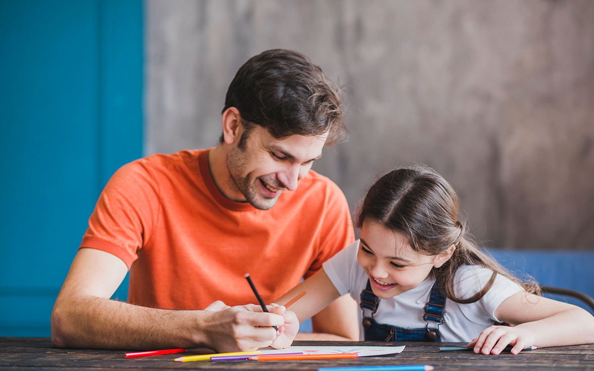 A father and daughter sit together at the table with pens and paper, they are learning about the present perfect tense.