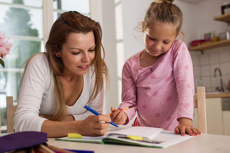 A mother and daughter are sat together learning about the present perfect tense, they have a pile of books in front of them.