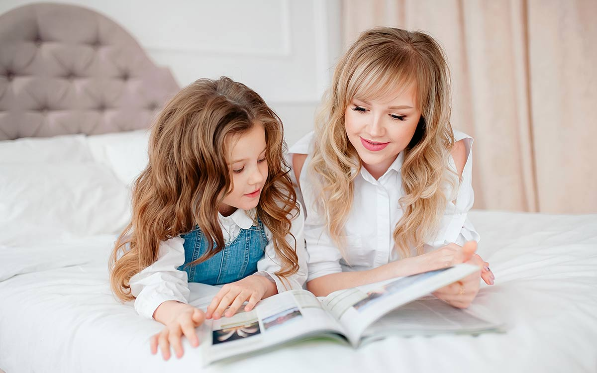 Mum and daughter lying on the bed reading a book, mum helping daughter to understand figurative language.