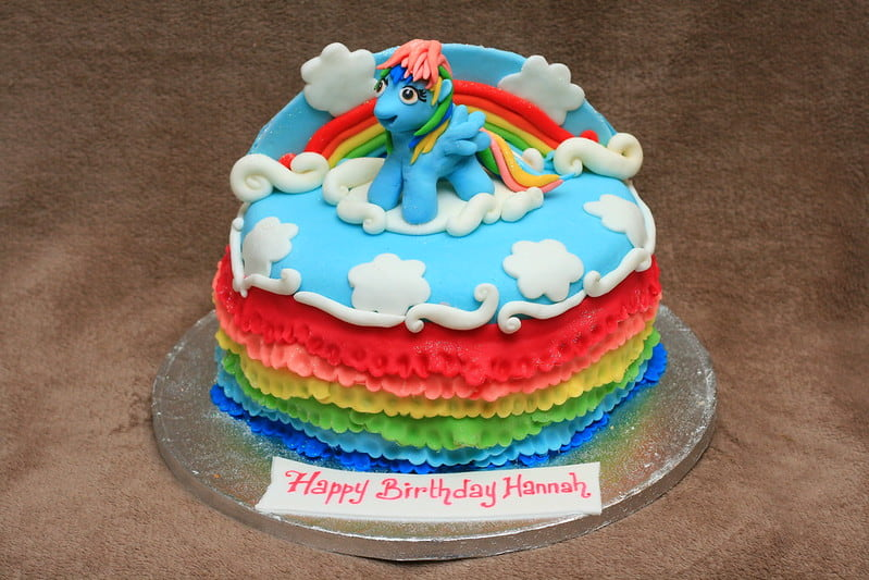 A My Little Pony Cake with blue icing on top, rainbow coloured icing stripes around the side and a My Little Pony character (Rainbow Dash) cake topper sitting on top.