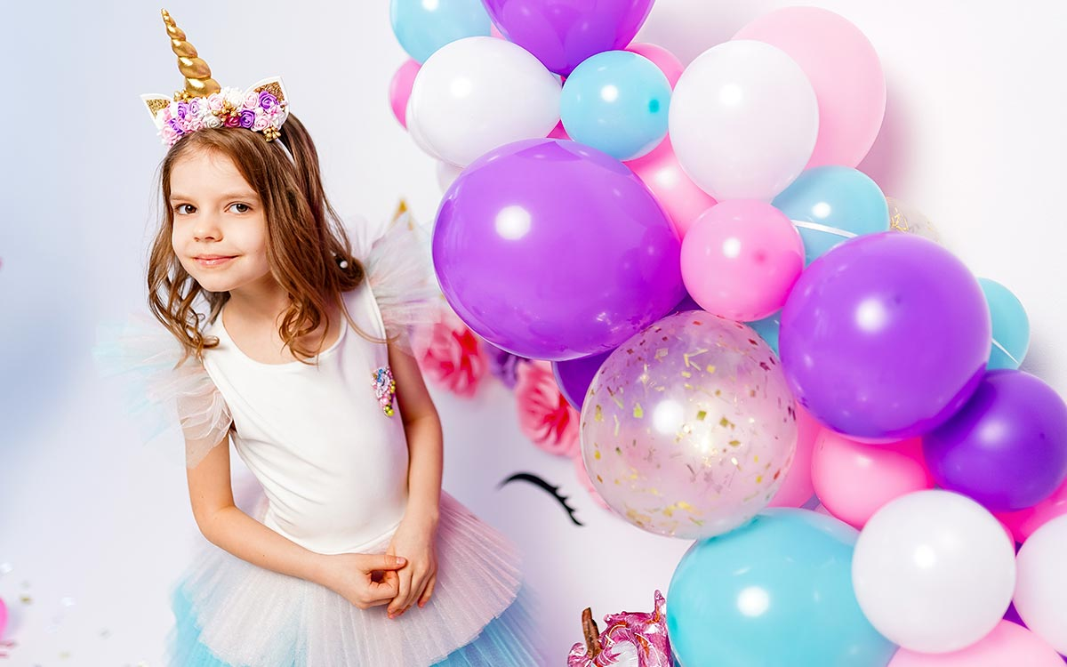 A young girl is dressed as a pony for a My Little Pony birthday party, she is stood next to a purple, pink, white and blue balloon display.