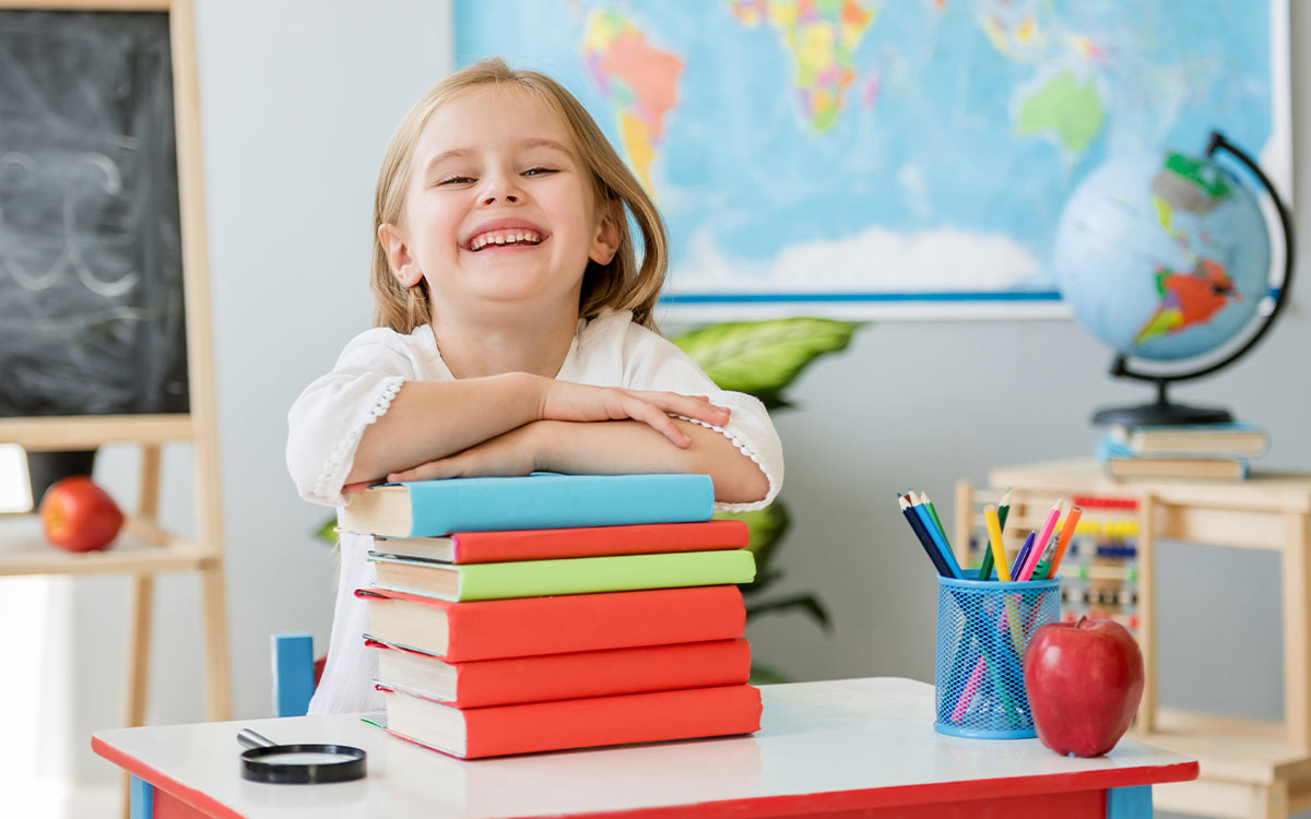 Girl standing in a classroom resting her arms on a pile of books smiling.