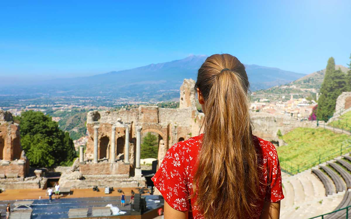 Young girl standing looking out over the view of ancient ruins in Greece.