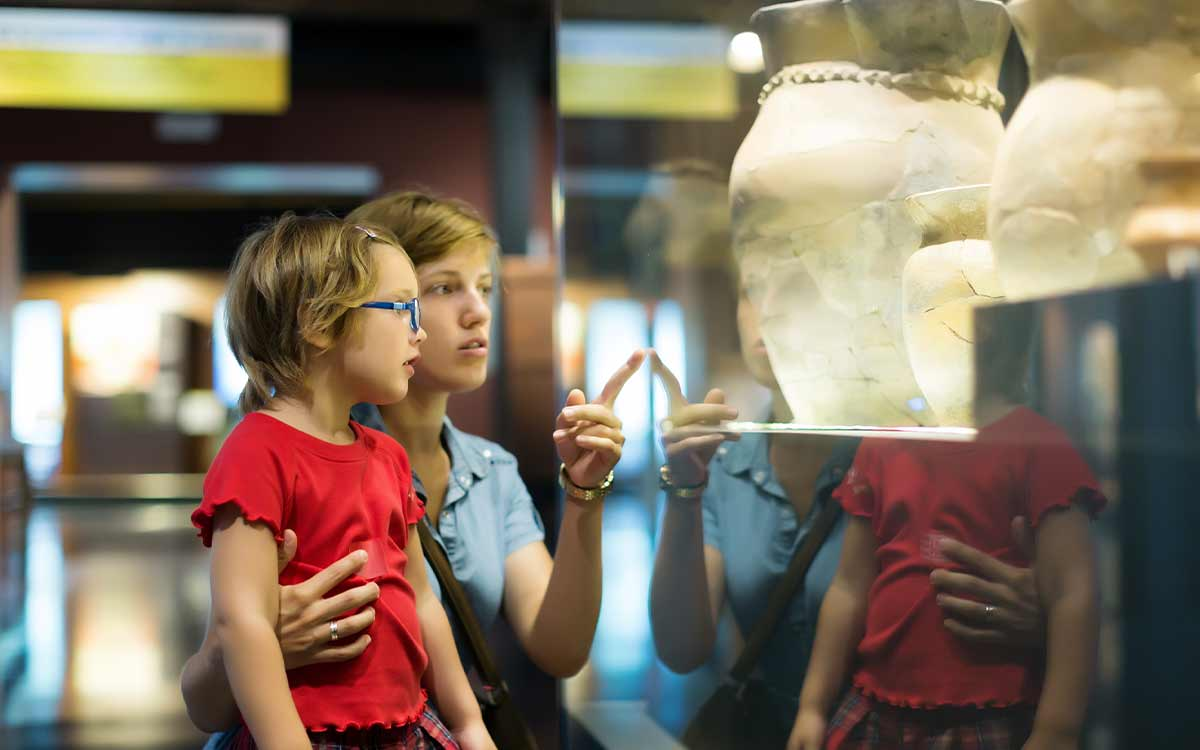 Mum pointing out Ancient Greek artefacts in a display cabinet in a museum to her daughter.