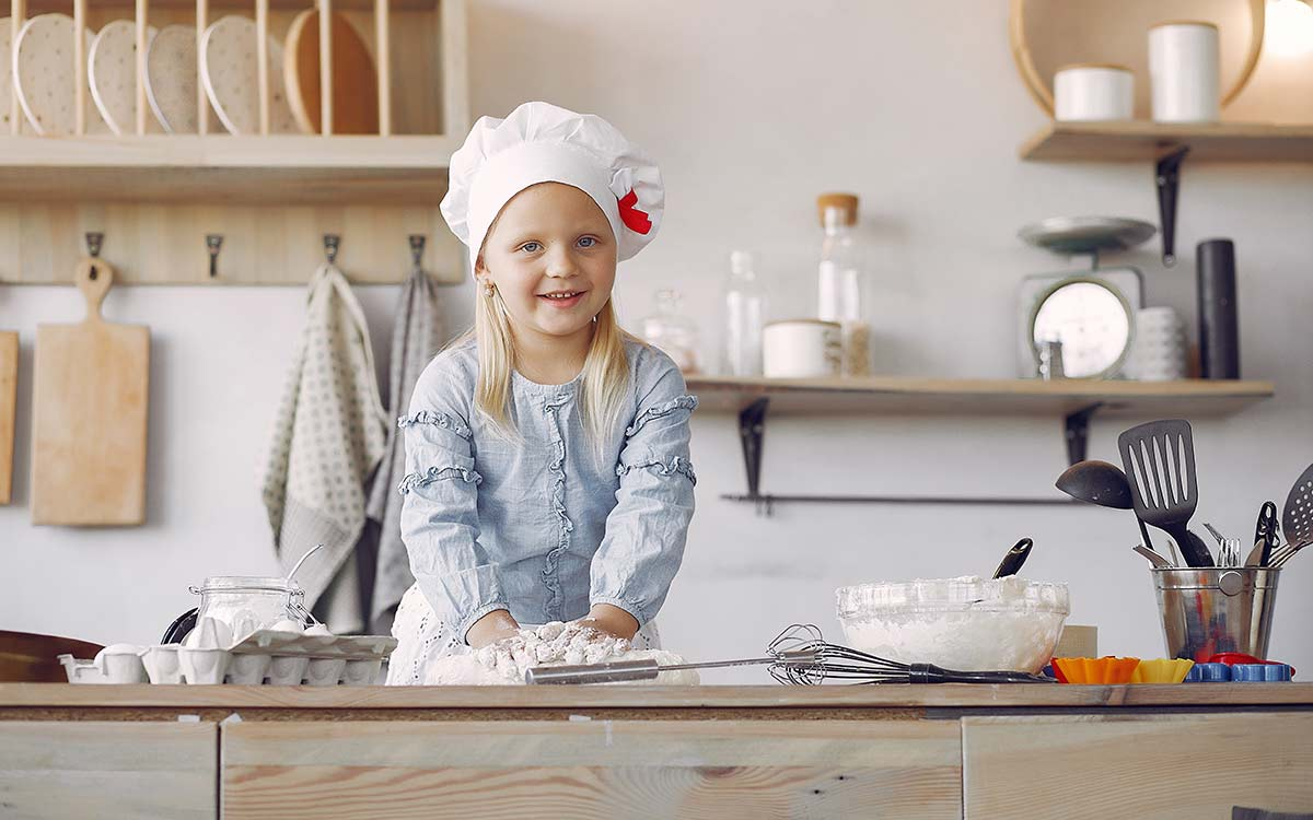 A little girl wearing a chef's hat is preparing ingredients for this giant cupcake recipe.