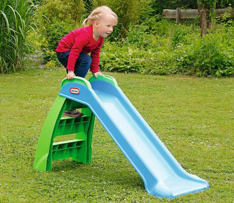 Child about to go down a blue and green garden slide.