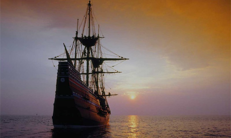 The Mayflower ship at sea with the sun on the horizon.