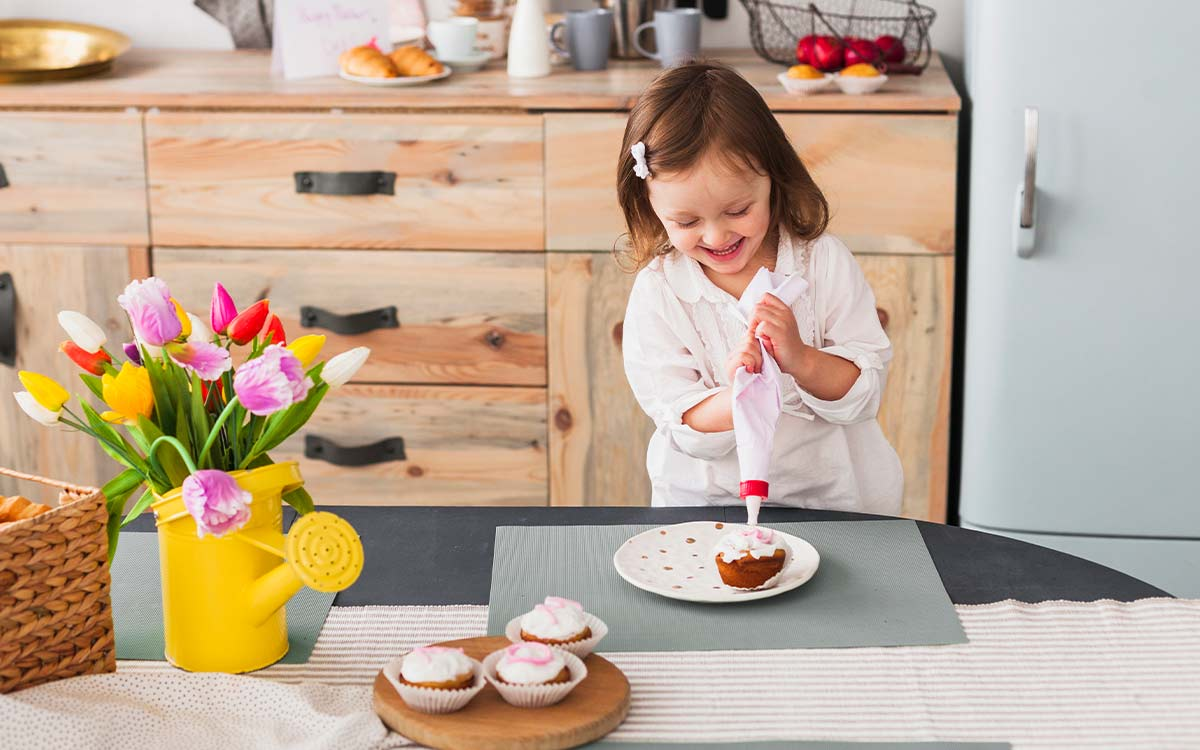 A young girl smiles as she uses a piping bag to ice some cupcakes.