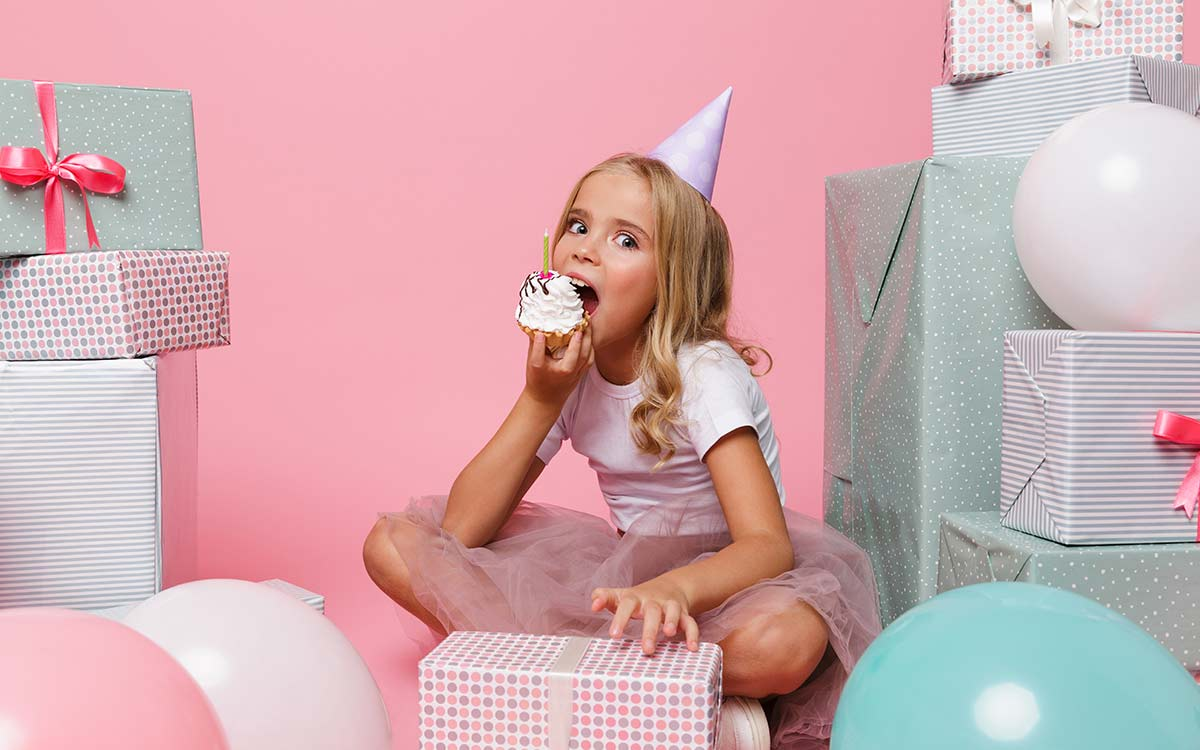 A young girl looks into the camera as she takes a bite of a cupcake, she is wearing a party hat and is surrounded by presents and balloons.