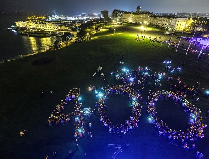 People stood in the shape of the number 400 lit up at night.
