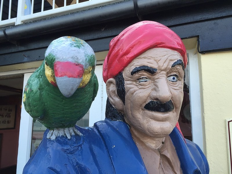Plastic statue of a pirate with a parrot on his shoulder.