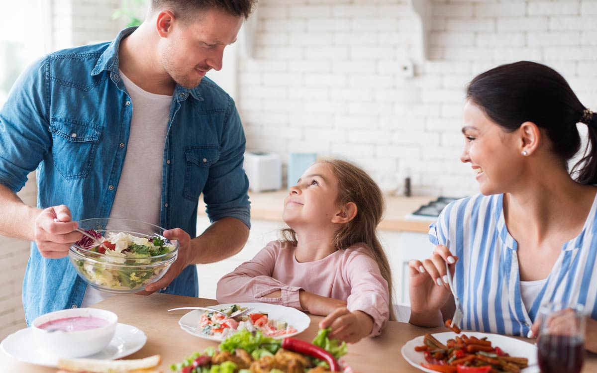 A family are sat at the table together sharing a meal, the salad they are eating will travel through the digestive system.
