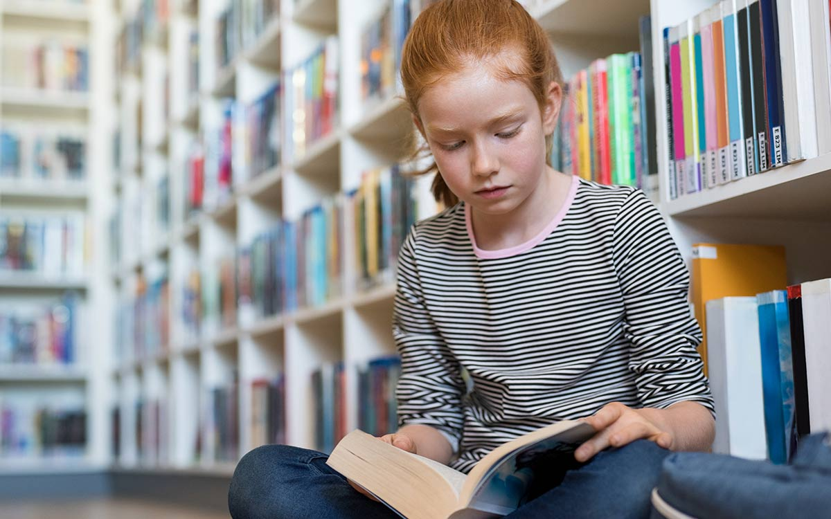 A young girl is sat cross legged on the floor of a library reading a book, she is learning about the digestive system.