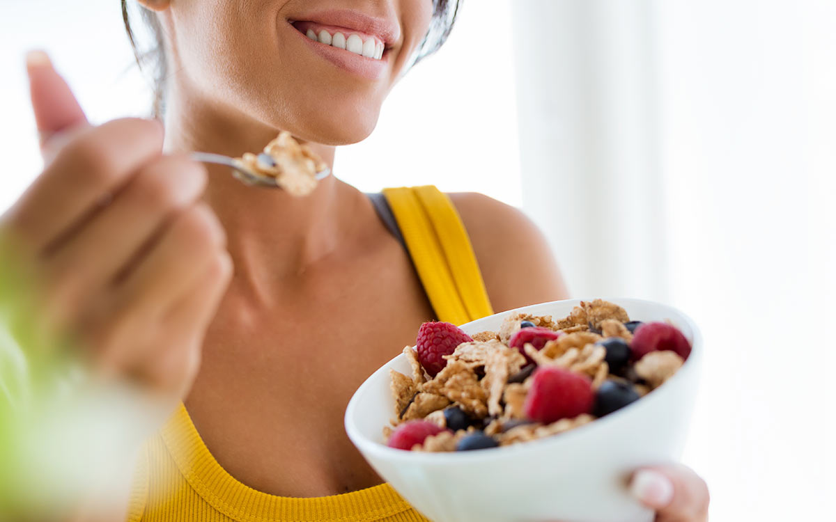 A close up image of a woman smiling as she eats a bowl of cereal representing the beginning of the digestive system.