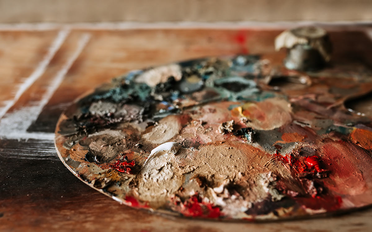 A wooden artist's palette covered in paint, representing the materials used in WW2 art.