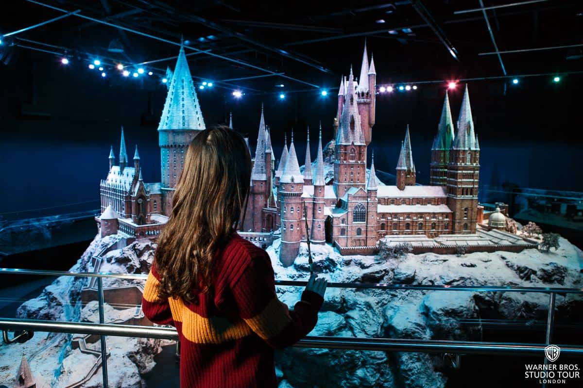Young girl, dressed in a Gryffindor jumper and holding a wand, looking at the Hogwarts model at the studio tour.