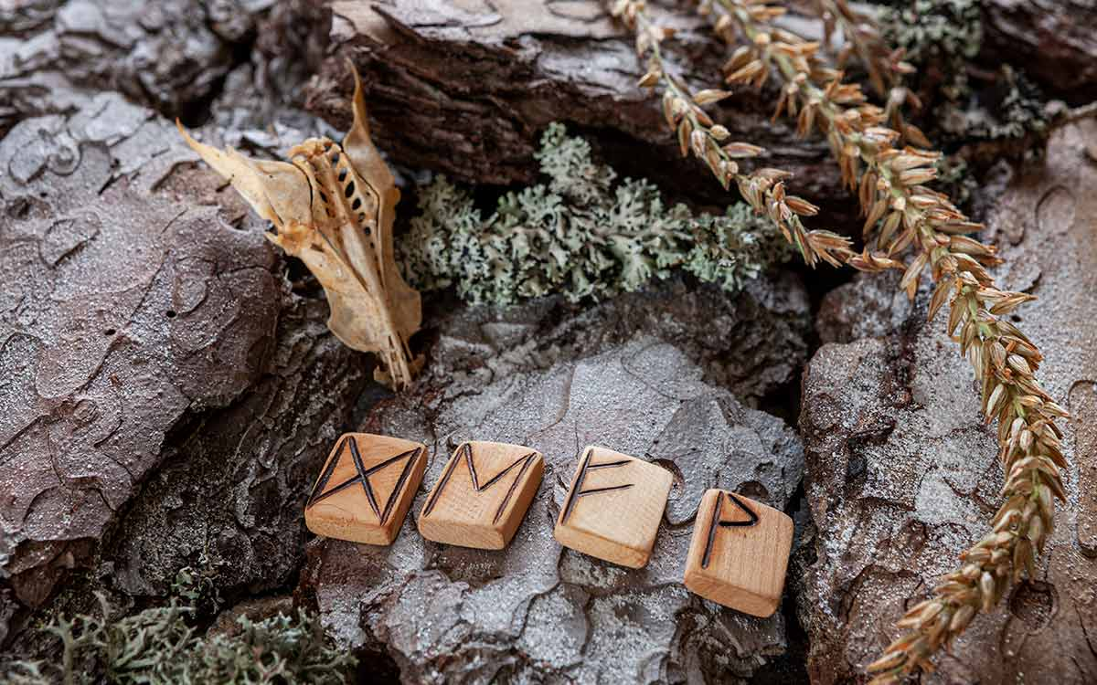 Four Viking runes written on blocks on wood placed on rocks.