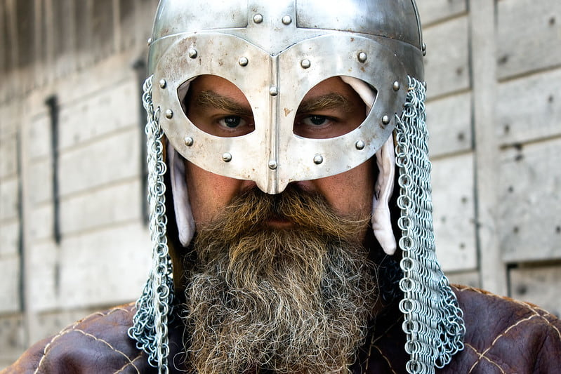 A Viking man wearing a Viking helmet looks straight at the camera.