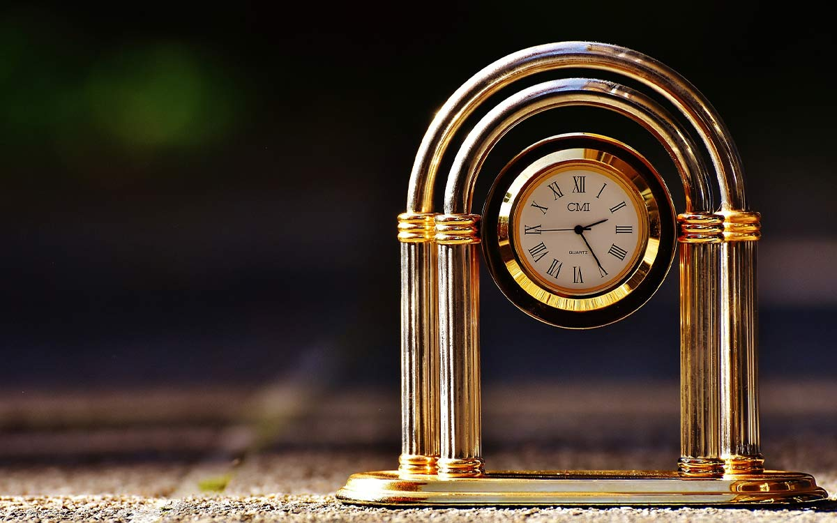 An image of a small gold clock which uses Roman numerals.