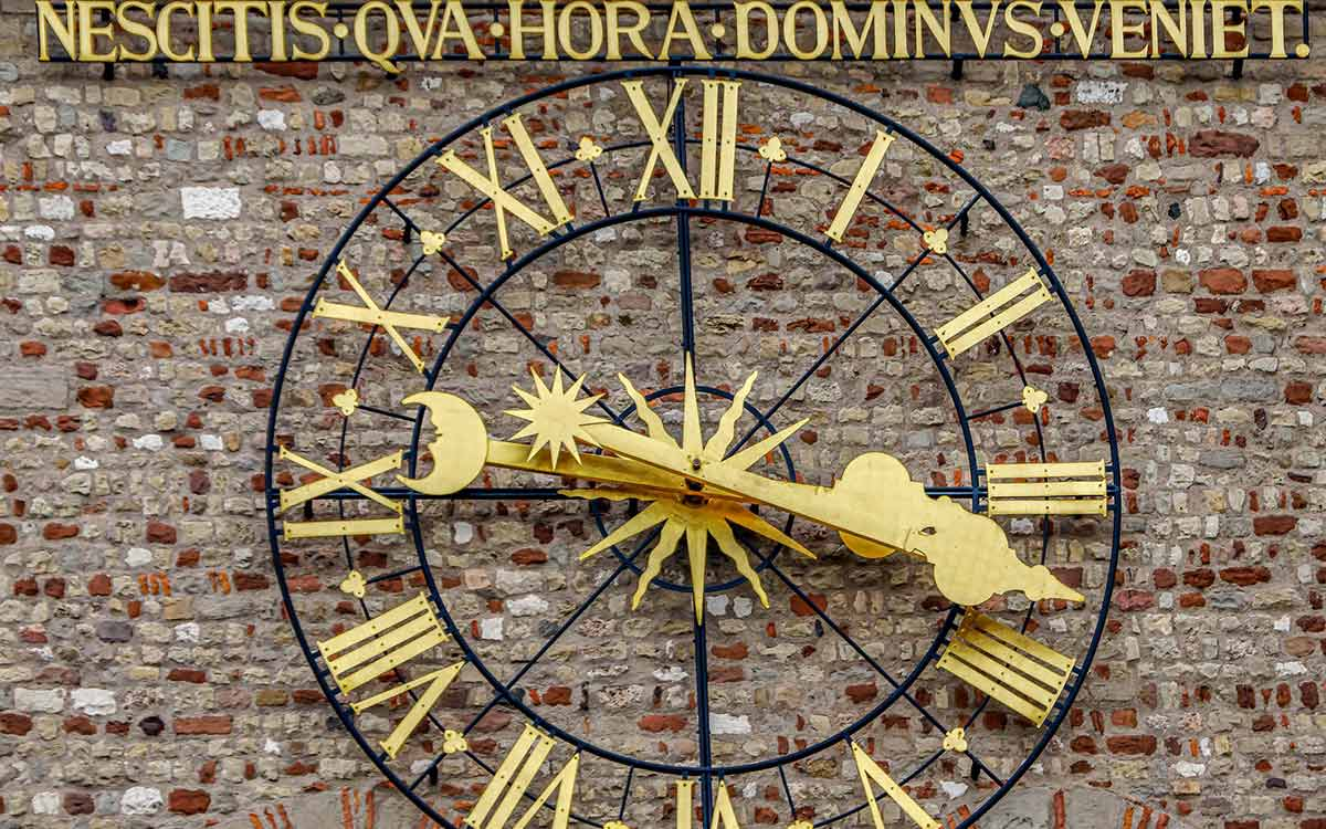 A large, ornate, gold clock face which uses Roman numerals.
