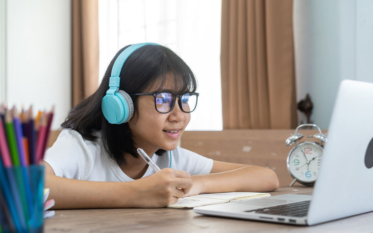 A girl wearing headphones and glasses using a laptop and notebook to learn about Roman numerals.