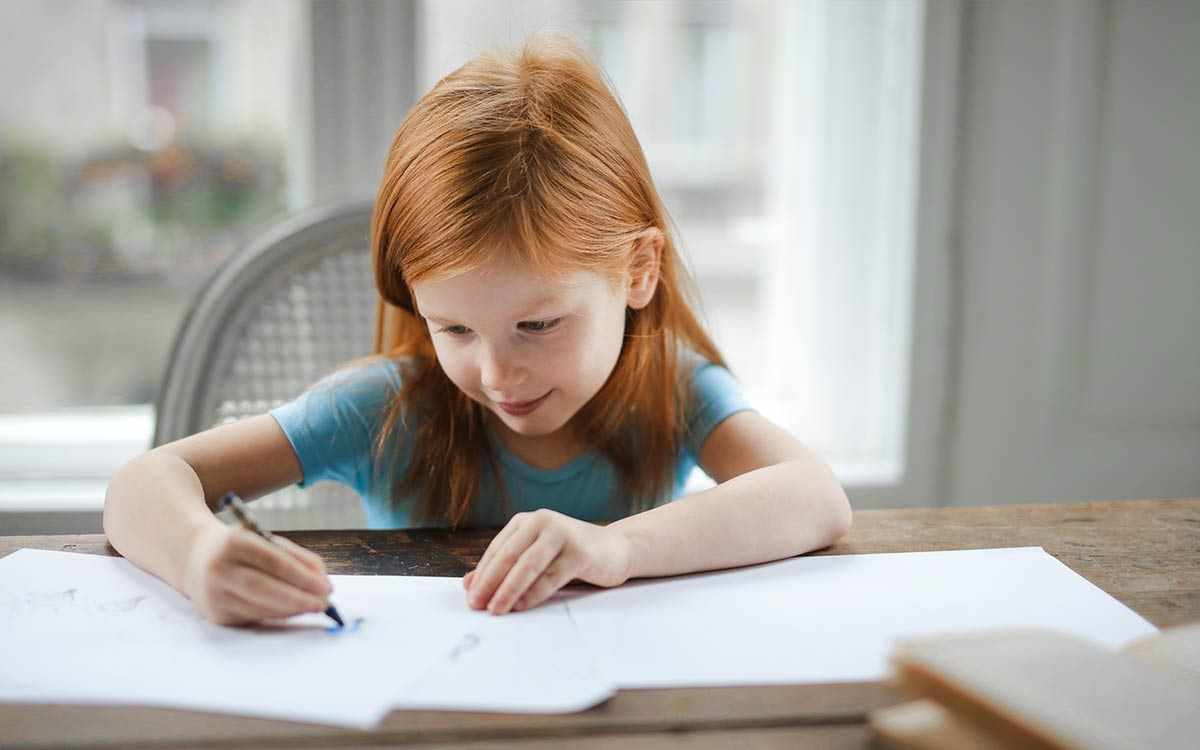 Young girl sat at a table writing about Stone Age tools in her workbook.