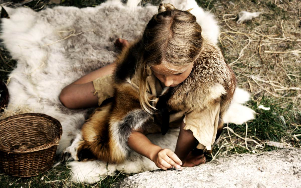 Little girl wearing fake animal furs like a Stone Age person.