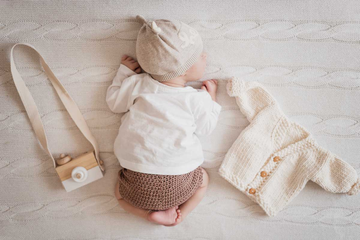 A baby wearing neutral colours is curled up on a blanket next to a toy camera and a knitted cardigan.