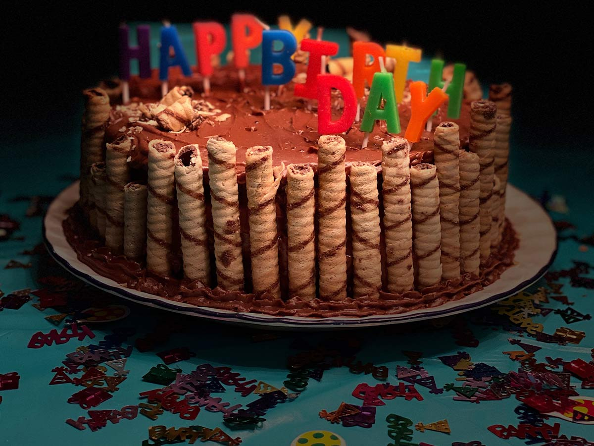 A chocolate cake topped with chocolate icing, with wafers rolls around the side and candles spelling 'happy birthday' on top.