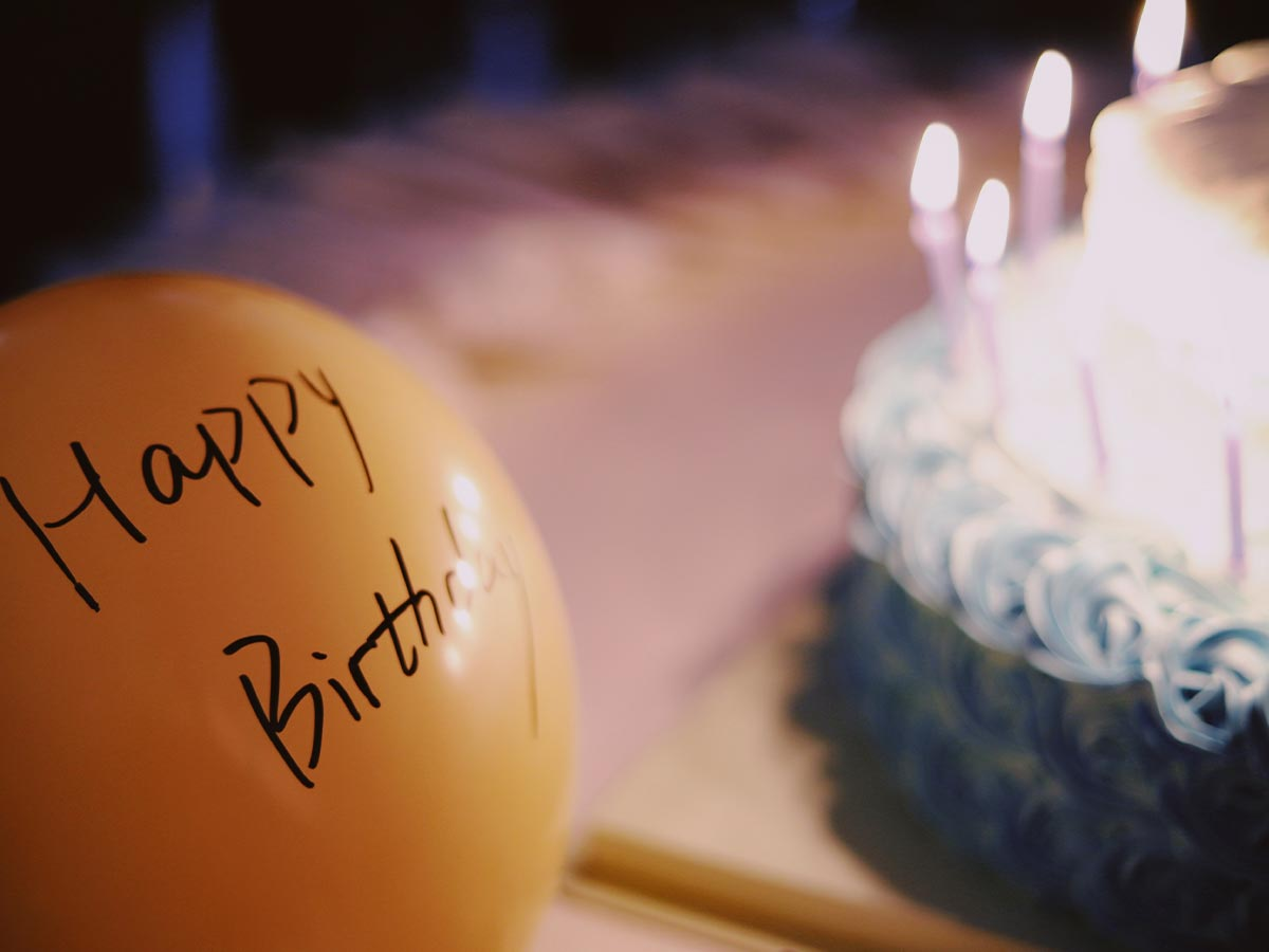 A yellow balloon with 'happy birthday' written on it, in the background is a birthday cake with lit candles.