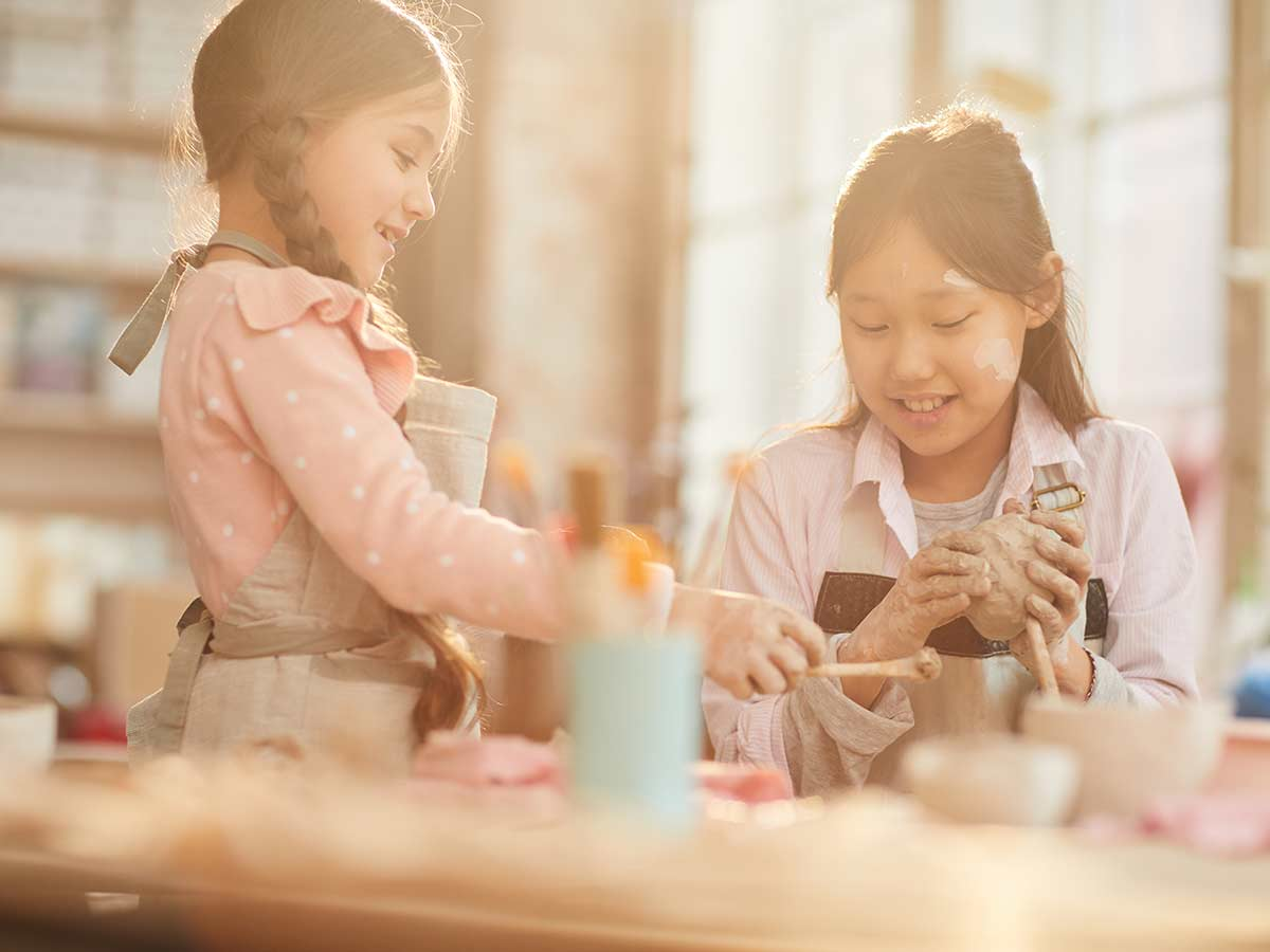 Two girls smile as they sit at a craft table together using clay to make a giraffe craft.
