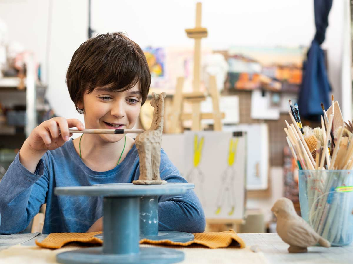 A boy smiles as he uses a craft tool to decorate a giraffe clay model.