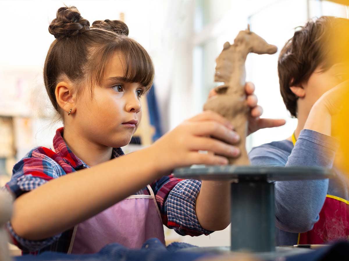 A young girls concentrates as she shapes some clay into the shape of a giraffe.