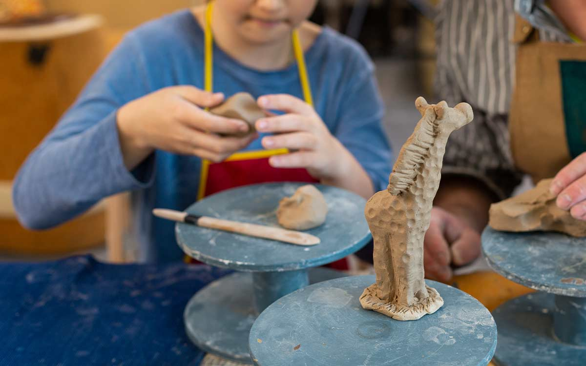 Close up image of a model giraffe, in the background a child uses clay to make a model giraffe craft.