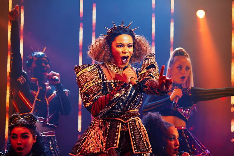 An actress playing one of Henry VIII's six wives singing on stage in Six The Musical.
