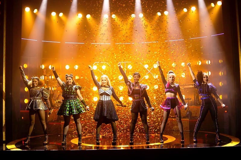 The cast of Six performing a song on stage with their fists in the air in front of yellow lights.