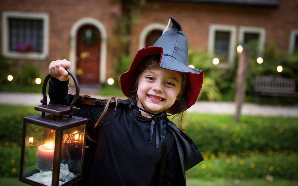 A young girl dressed as a witch for Halloween smiling at the camera and holding up a lantern.