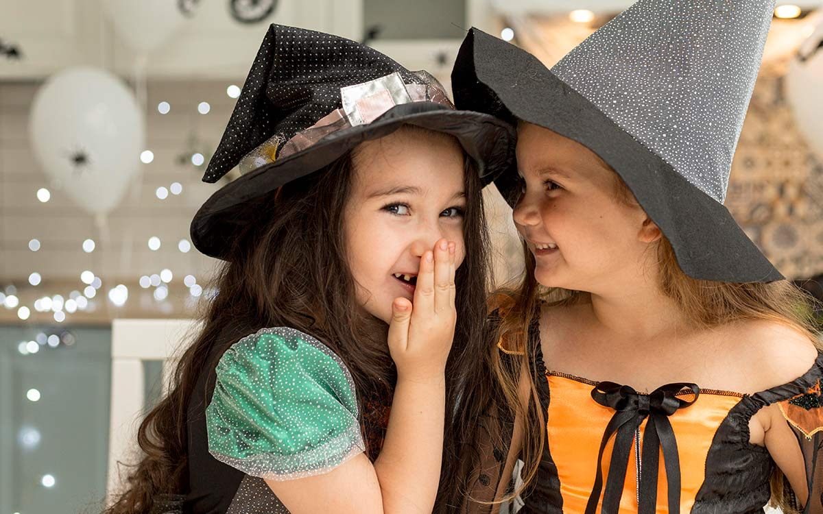 Two young girls dressed in Halloween witch costumes, one smiles at her friend whilst the other looks at the camera.