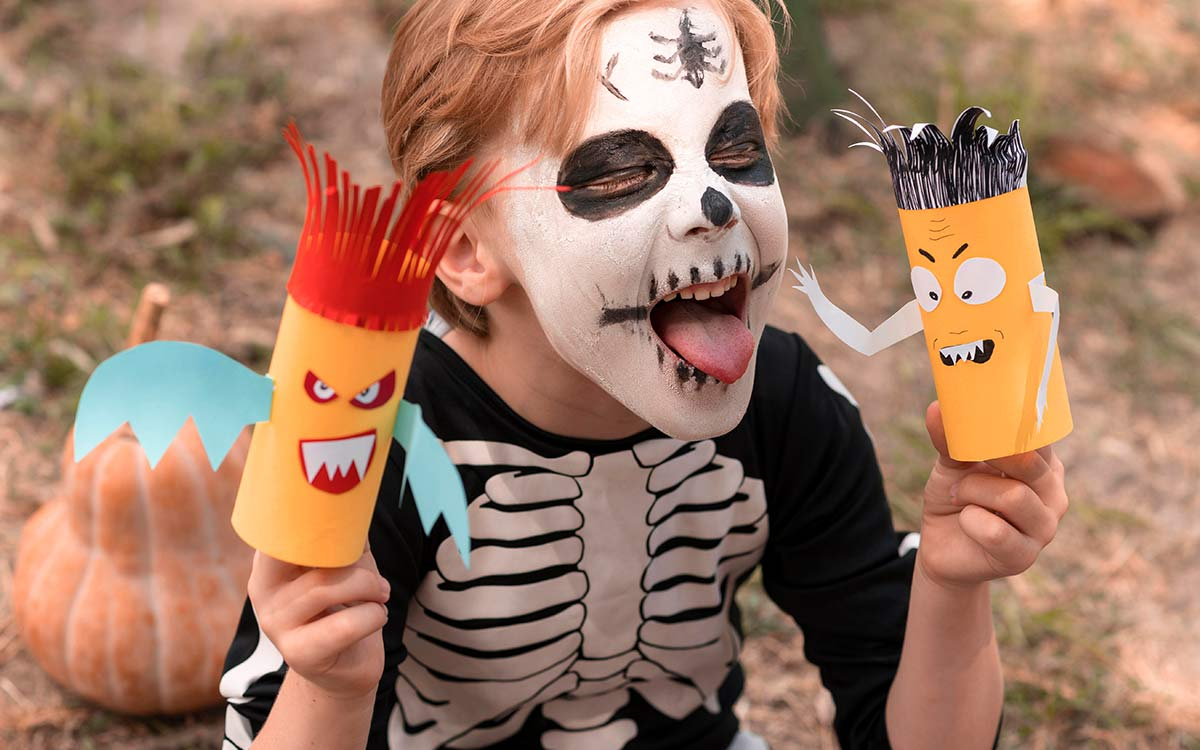 A young boy dressed as a Halloween skeleton with skeleton face paint sticks his tongue out whilst holding some Halloween crafts.