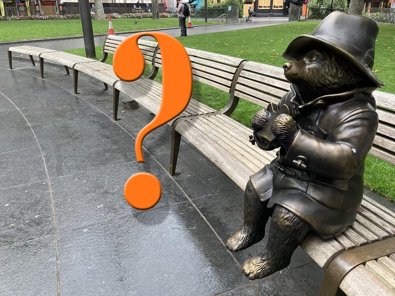 Statue of Paddington Bear in Leicester Square with a question mark graphic next to him for the mysterious new statue.