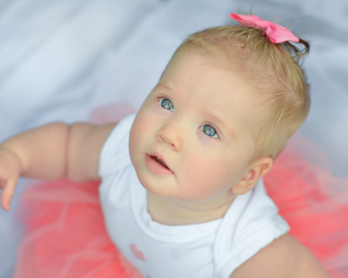 A photo taken from above of a baby girl wearing a pink tutu and a pink bow in her hair who is looking up towards the camera.
