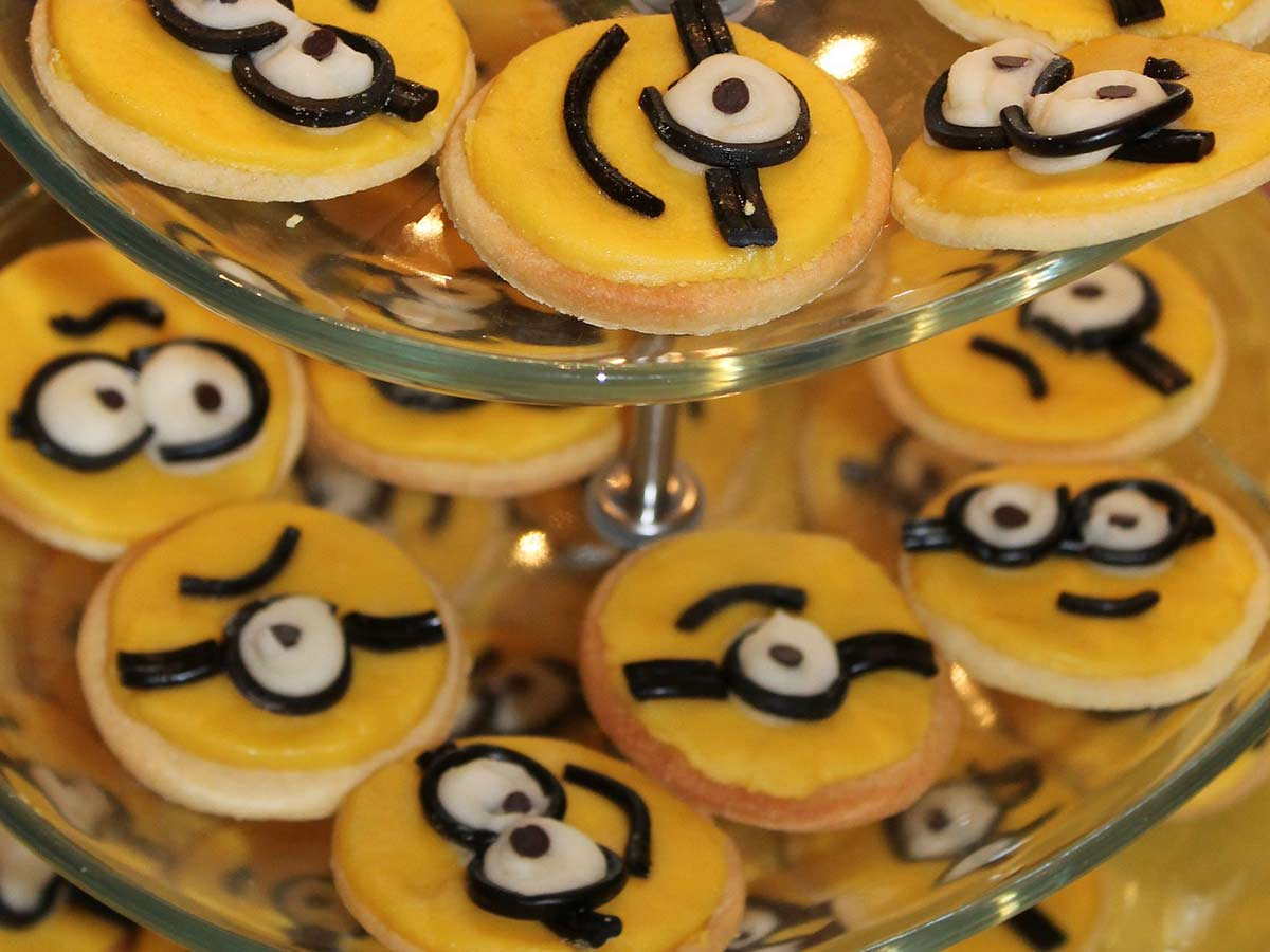 Lots of round, yellow minion cookies displayed on a cake stand.