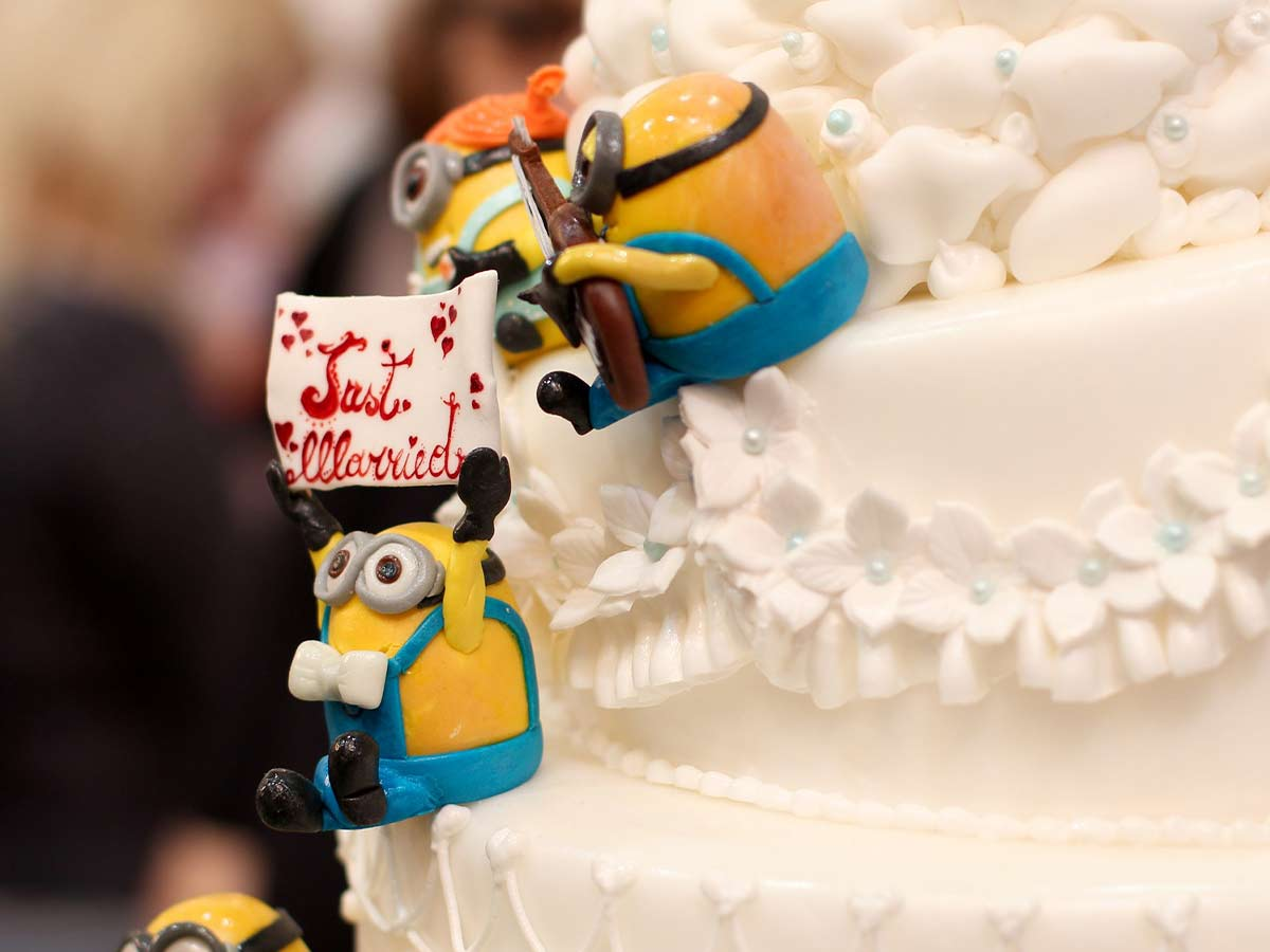 Three fondant minions sitting on the side of a large white cake.