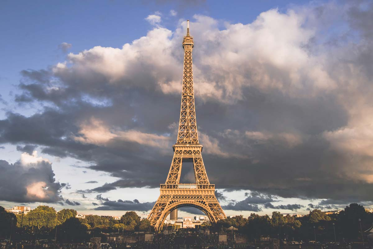 The Eiffel Tower in Paris with a cloudy sky behind it.