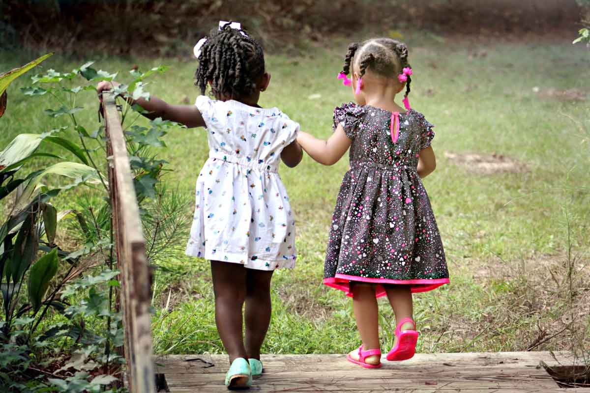 Two little girls walking hand in hand in the park.