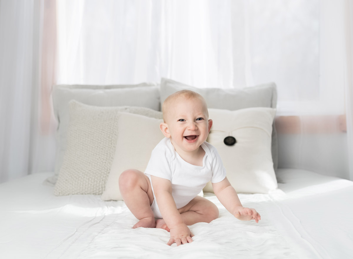 Happy baby, wearing a white baby grow, sat on the bed smiling and laughing.